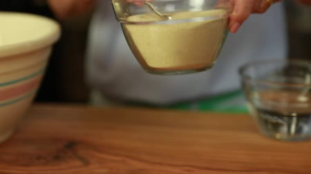 medir : a woman puts yeast in beer bread dough