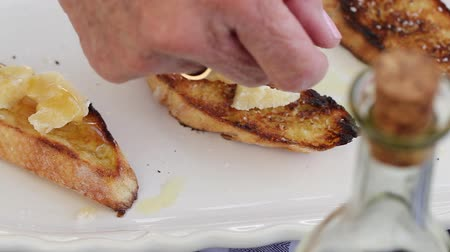 bruschetta : a woman puts parmesan cheese and honey on bruschetta Stock Footage