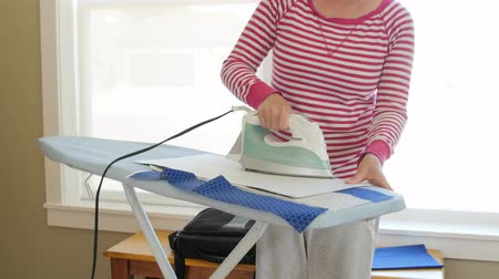 vyšívání : A woman irons her sewing projects