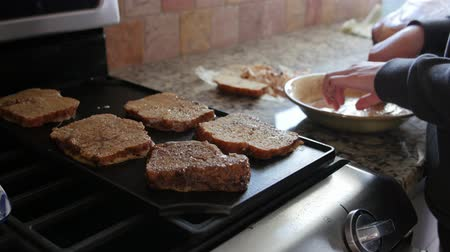 fried : A woman makes french toast for breakfast in the kitchen