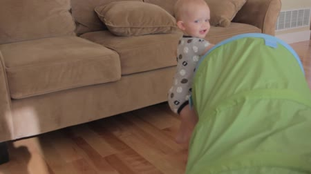 baby boy playing with a green tunnel Stock Footage