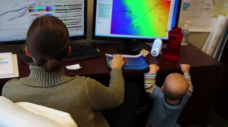 papelada : a woman geologist working in an office space with her baby