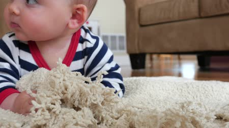 otcovství : A baby plays on his blanket on the floor