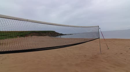 volleyball : A volleyball net set up on a sandy beach and ocean cove.