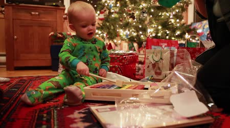 ailelerin : boy opening christmas presents in pajamas