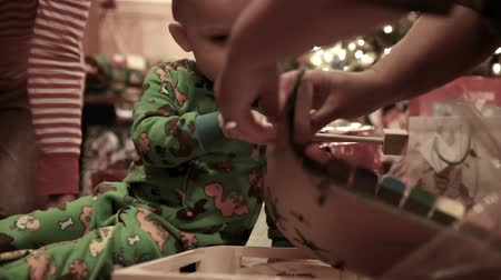 slavnosti : boy opening his christmas presents in his pajamas