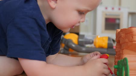Boy playing with toy robot on the floor Stock Footage