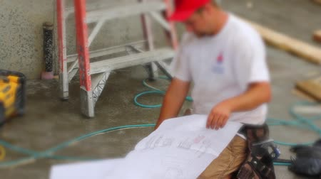 vállalkozó : Contractor reviewing architectural house plans at a construction site