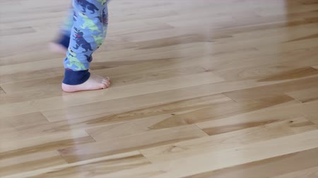 burmak : A little boy twirls on a wood floor in his home staring at the camera