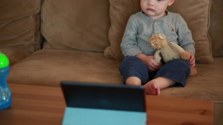 sofá : a toddler boy watching a movie on an tablet