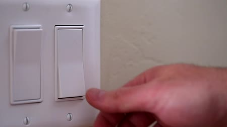 comutar : a dolly shot of a hand turning on a light switch