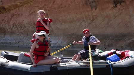 families rowing river rafts down the san juan river by cliff Stock Footage