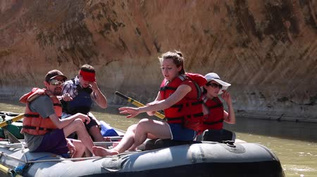 families rowing river rafts on san juan river by cliff