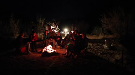 kamp ateşi : families sitting around a campfire at night