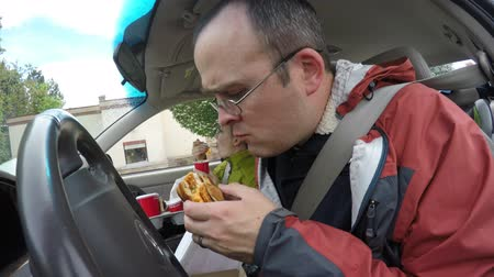 Family eating fast food in their car traveling