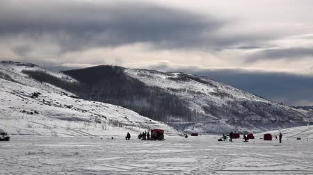 broca : Family ice fishing on a reservoir in the snowy mountains Stock Footage