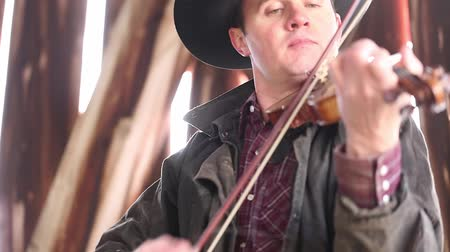 buty : A cowboy plays the fiddle for a square dance in a cool old barn. The sunlight can be seen pouring through the old wooden boards Wideo