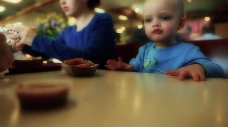 картофель фри : a family sitting in a booth at a fast food restaurant eating food