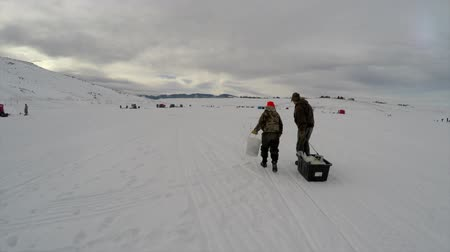 otcovství : father and son walking across a lake to go ice fishing