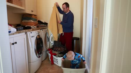 моющее средство : a toddler helps his dad put clothes in the washing machine