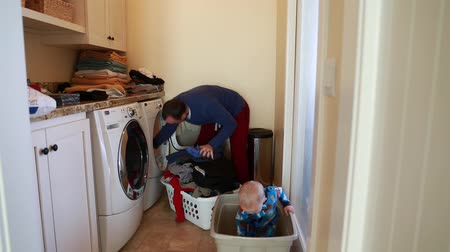 otcovství : a toddler helps his dad put clothes in the washing machine
