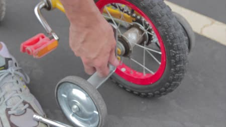 csavarkulcs : father puts training wheels on bike