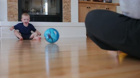 pisos : A little boy plays with his father by rolling a ball across the floor