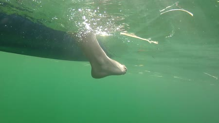 descanso : Foot hanging in water off kayak