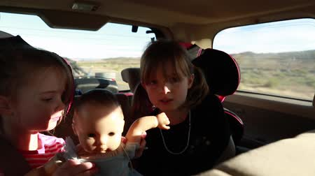 долл : girls sitting in car seats in an suv traveling with their family. Стоковые видеозаписи