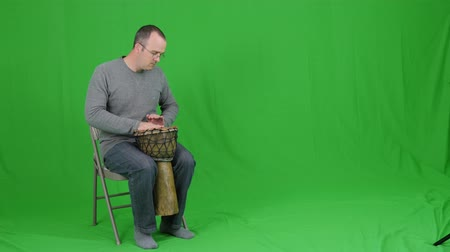 bicí nástroje : A green screen shot of a man playing a cool wooden drum