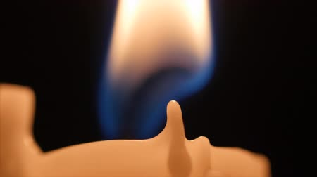 ember : Lighting a wax candlestick in a dark room