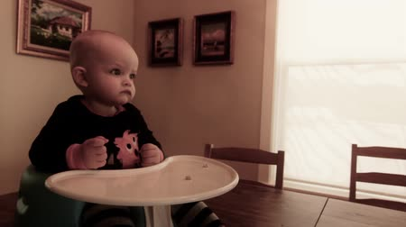 kabine : a baby sitting on kitchen table eating