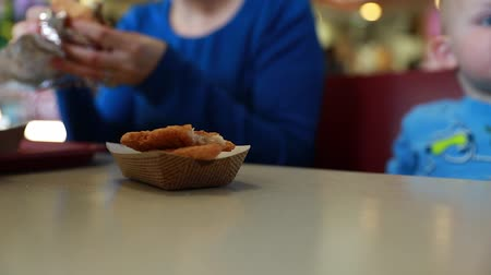queijo cremoso : a family sitting in a booth at a fast food restaurant eating food