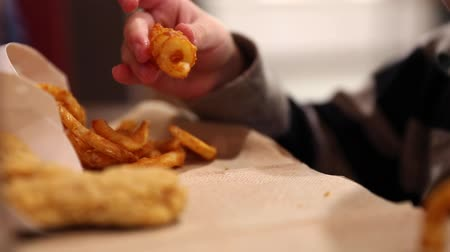 fry : little boy eating curly fries Stock Footage