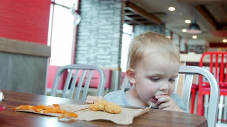 frango : A young mother with her toddler son eating a lunch at a clean and modern fast food restaurant Stock Footage