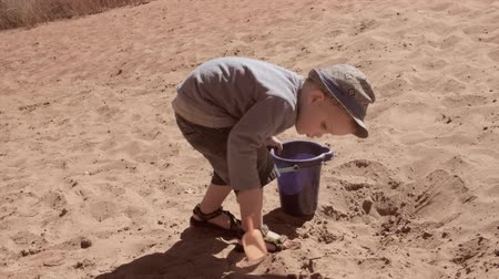 klapki : Little boy filling a bucket with sand on beach