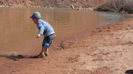aventura : A little boy plays in a sandy beach on the bank of the Green River near Moab utah Vídeos