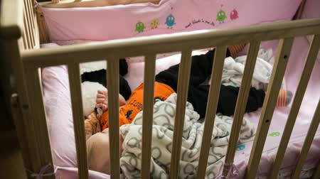 acorde : a little boy waking up in his crib from his nap time lapse