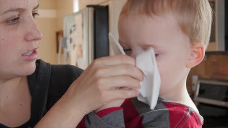 tosse : A mother holds her sick little toddler in her arms while he blows his nose into a tissue