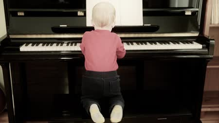 пианино : little toddler playing on the piano
