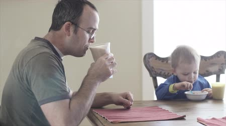 wapń : A man drinks a healthy shake for breakfast while his toddler eats cereal at the table