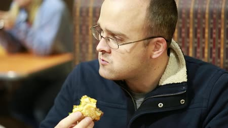 appetito : un uomo mangia un hamburger in un fast food Filmati Stock