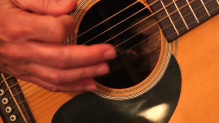 acoustical : Man playing the guitar in a band close up