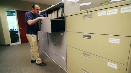 kabine : a man looks through large filing cabinets at a business