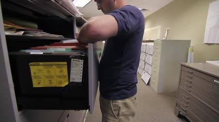 papelada : man looking through file cabinets
