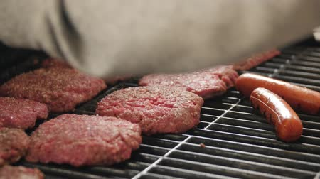 grilling : Man seasoning hamburgers and hot dogs on grill