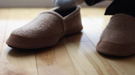 klapki : man slips on a pair of slippers dolly shot