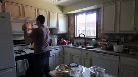 reheat : A man heats food in the microwave