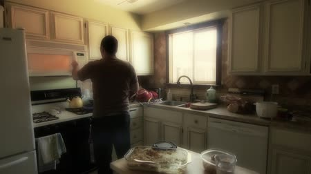 reheat : A man takes food out of the microwave. Stock Footage