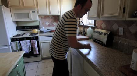 szervez : A man cleaning his kitchen